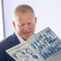 Brian Kelly looking at a book with a guest at the Jamie Hosford Football Center dedication.